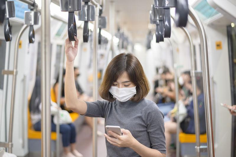 Young woman wearing mask using smart phone at subway train