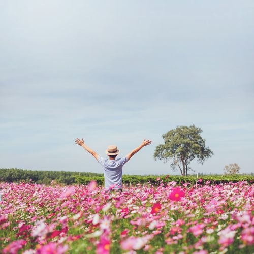 Person standing by flowers on field against sky