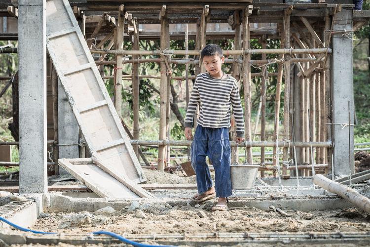 Portrait of smiling boy standing against built structure