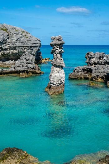Stack of rocks in sea against blue sky