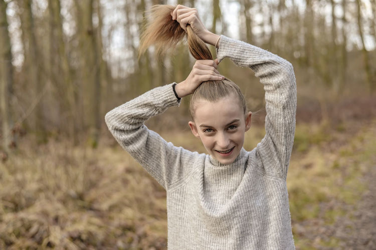 Portrait of smiling teenage girl tying hair in forest