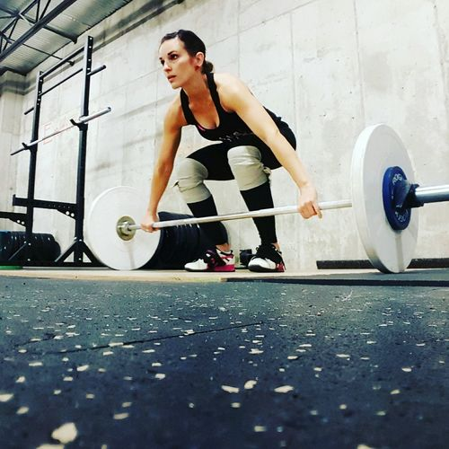 Low Angle View Of Woman Performing Deadlift