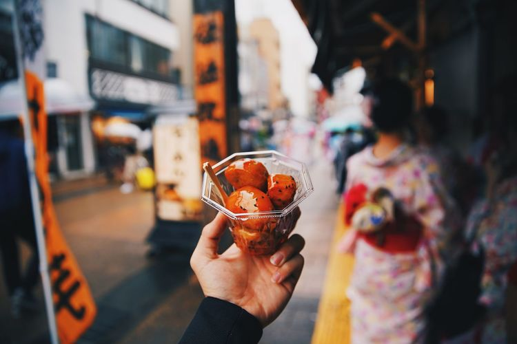 Midsection of man holding ice cream in city