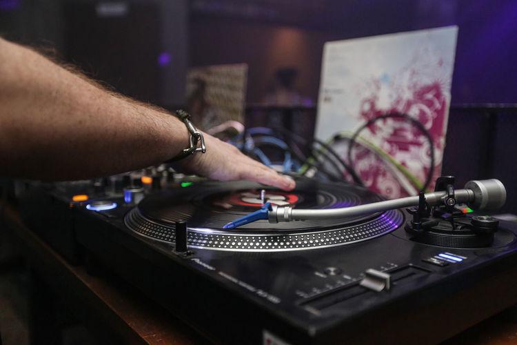 Cropped image of dj using sound mixer machine in nightclub