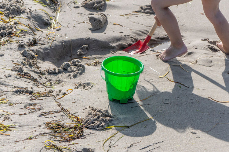 Nature Day Outdoors Summer People Bucket Playing Childhood Beach Sand Human Body Part Power Energetic Lifestyles Vacations Kid Child Standing Shovel Body Part Leisure Activity Low Section Human Foot