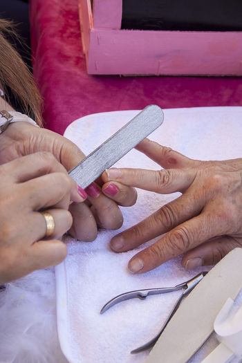 Cropped Hands Of Beautician And Woman At Beauty Parlor