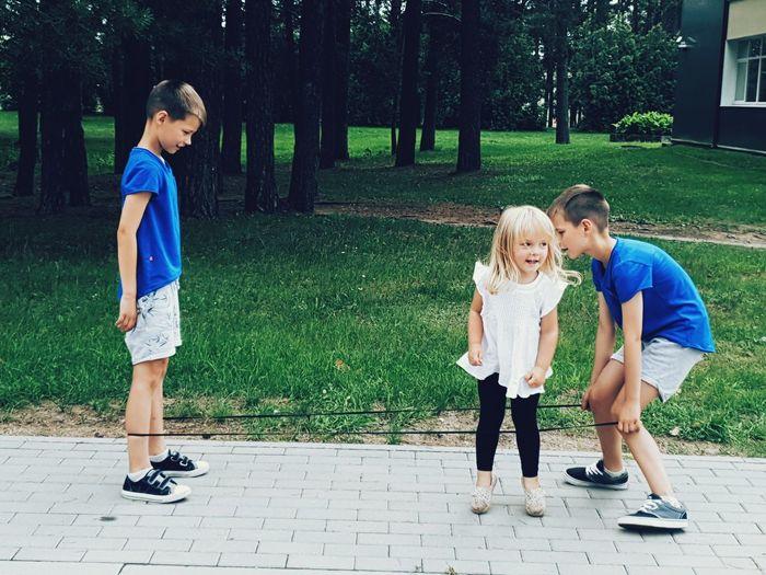 Full length of siblings playing on footpath in park