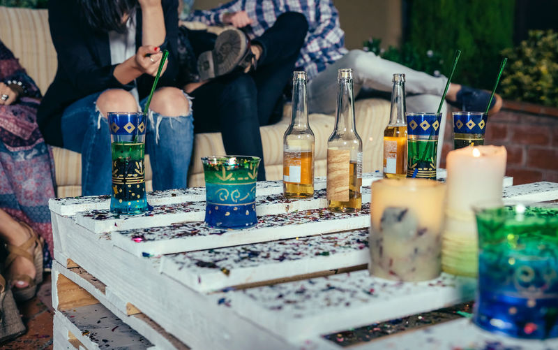 Close up of beverages over pallets table with confetti in a outdoors party with people talking in the background Beer Beverage Celebration Cocktail Friends Horizontal Millenial Sitting Spoon Terrace Alcohol Bottle Caucasian Cold Confetti Friendship Glass Group Night Nightlife Pallets Party People Table Youth Culture