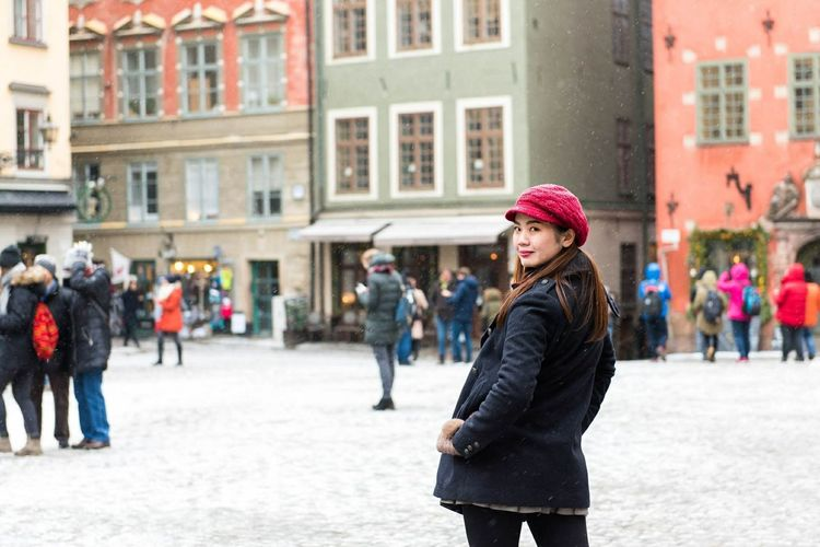 Woman Standing On Street In City During Winter