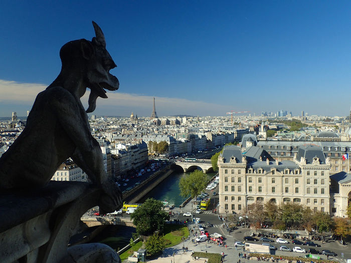 Statue Overlooking Cityscape Against Sky
