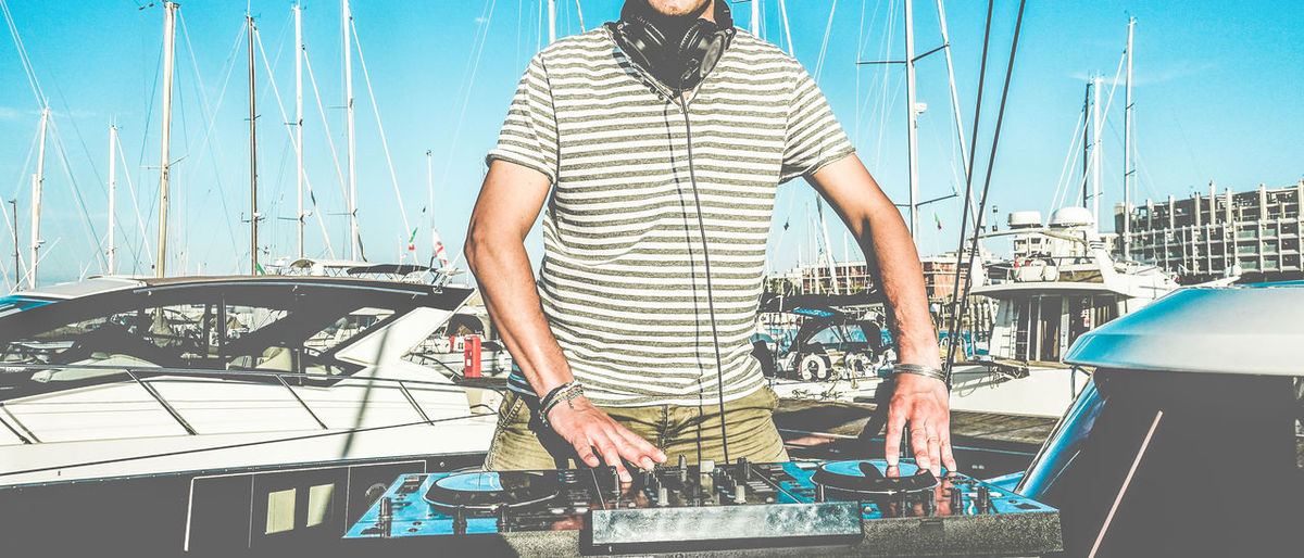 Midsection Of Dj Playing Music On Turntable While Standing On Yacht