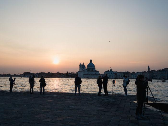 People at seaside during sunset