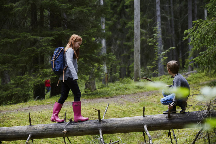 Full length of mother and daughter in forest
