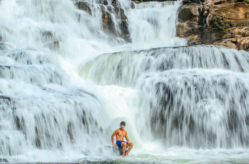 Shirtless Man Sitting Against Waterfall