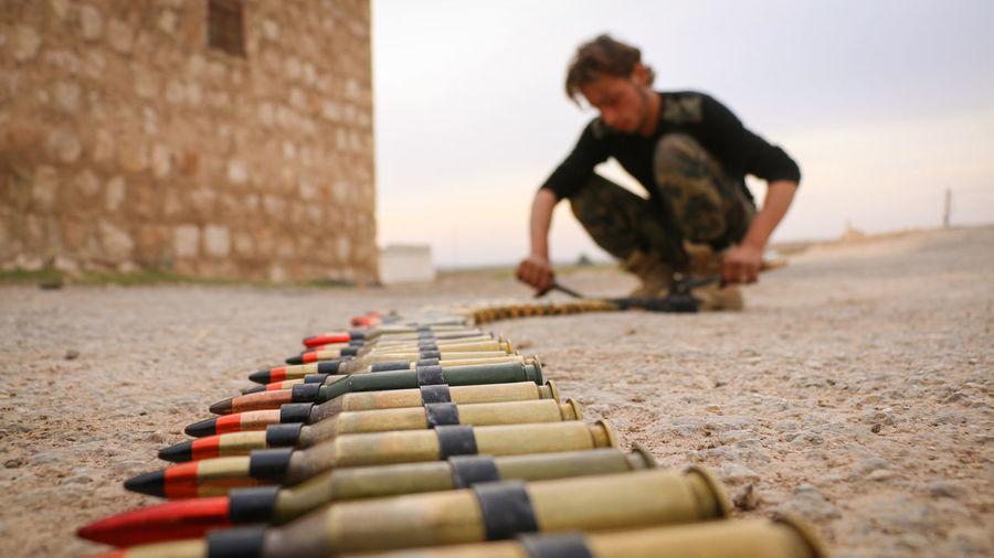 Full length of man arranging bullets on land against sky