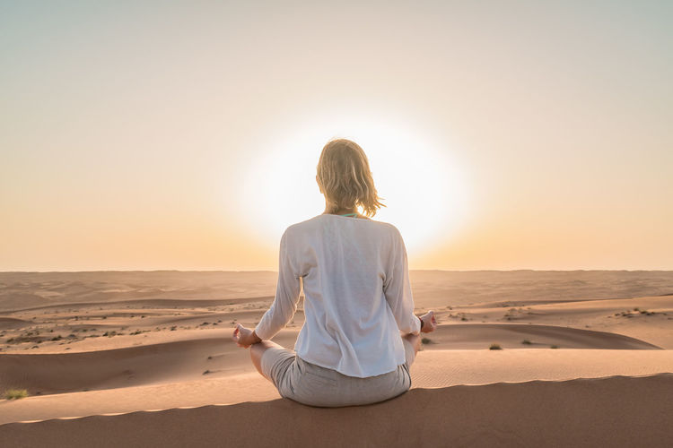 Desert Healthy Lifestyle Meditate Meditate, Contemplate, Think, Consider, Ponder, Muse, Reflect, Deliberate Meditation Nature Oman One Person Rear View Sand Sea Sky Sunlight Sunset Wahiba Sands Women Yoga