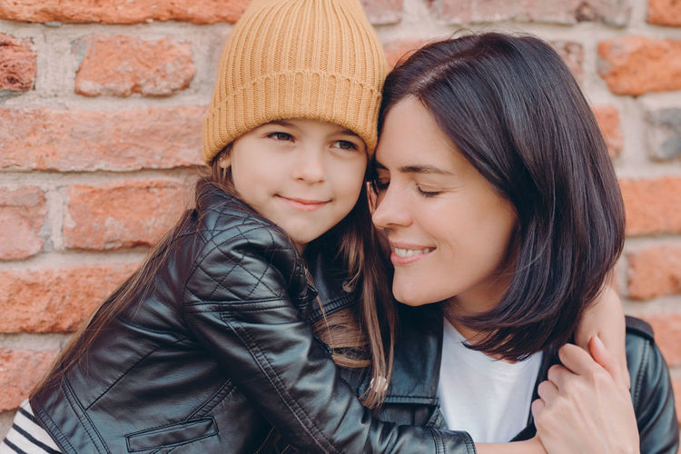 Close-up of girl embracing mother against brick wall