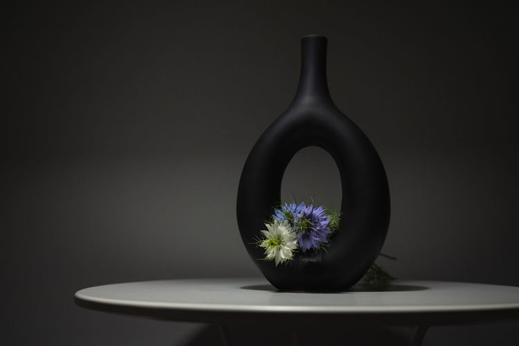 Close-up of white flower on table against black background