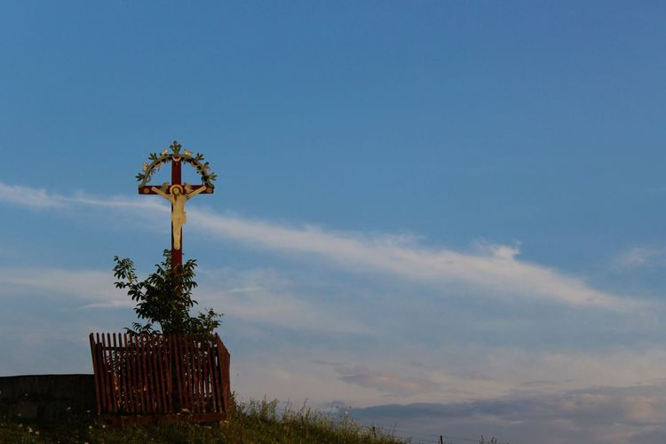 Crucifix on mountain against sky