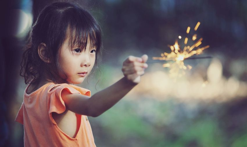 Cute girl holding illuminated sparkler outdoors