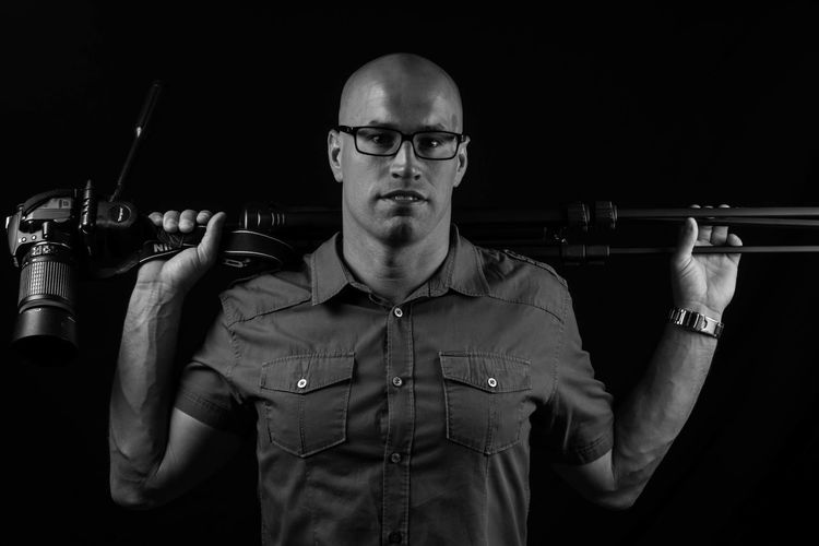 Portrait Of Bald Young Man With Camera On Tripod Standing Against Black Background