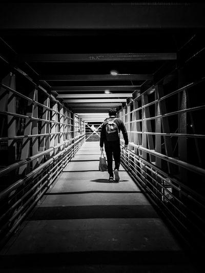 Rear view of man walking on covered bridge