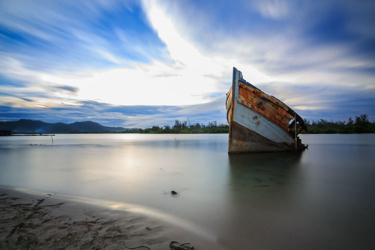 Abandoned Ship during sunset moment at sabah borneo malaysia Image has grain or blurry or noise and soft focus when view at full resolution. (Shallow DOF, slight motion blur) Abandoned Beach Beauty In Nature Cloud - Sky Day Lake Mode Of Transportation Nature Nautical Vessel No People Non-urban Scene Outdoors Reflection Scenics - Nature Sinking Sky Tranquil Scene Tranquility Transportation Water