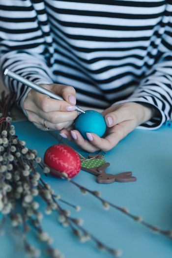 Midsection of person hands painting eggs on table