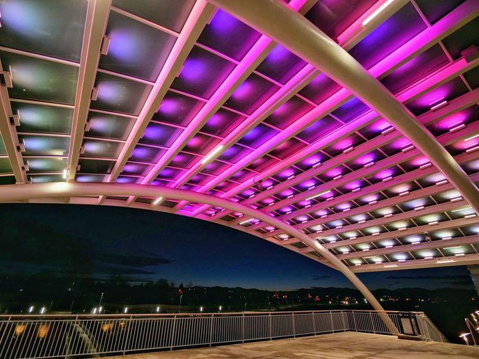 Low angle view of illuminated bridge at night