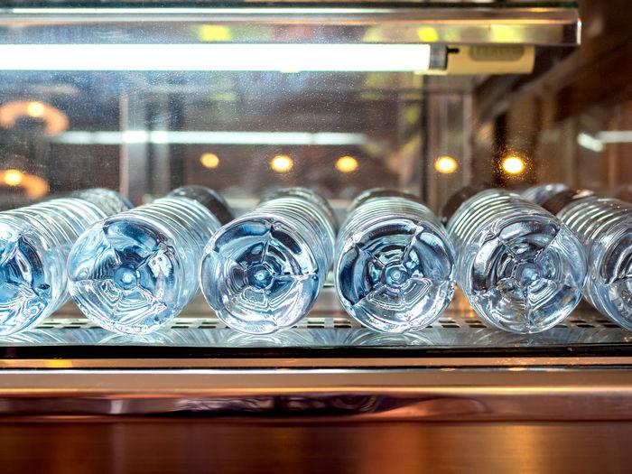 Bottles in refrigerator seen through glass door