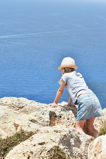 Girl Standing On Rocks At Beach