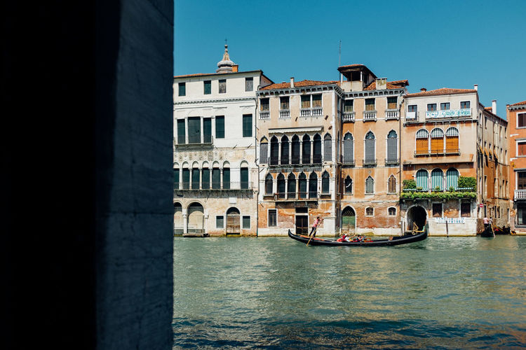 Gondola sailing in grand canal by old buildings against clear blue sky