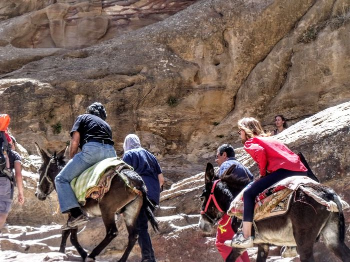 People riding donkey while climbing by rock formation
