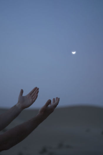 Person hand against moon in sky