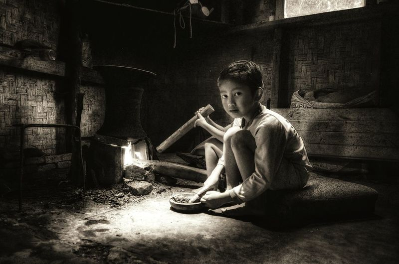 Portrait of boy by wood burning stove