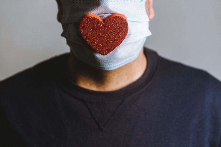 Close up of a man wearing a spongy heart on a face mask