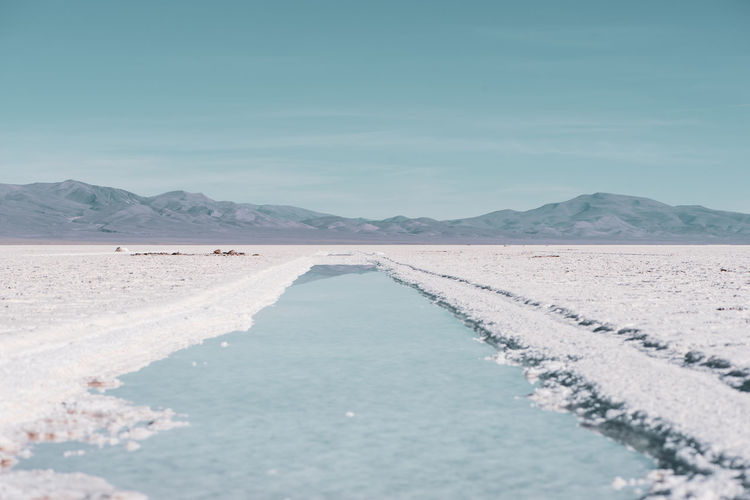 Scenic view of salt flat against sky