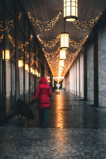 Rear View Of Woman Walking In Illuminated Corridor