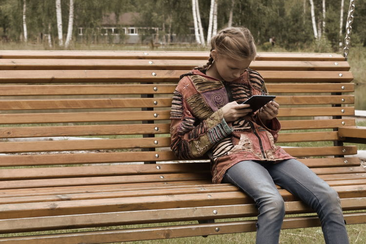 Girl using digital tablet while sitting on bench in park