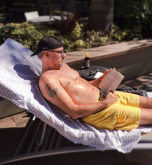 High Angle View Of Mature Man Sitting On Lounge Chair And Reading Book