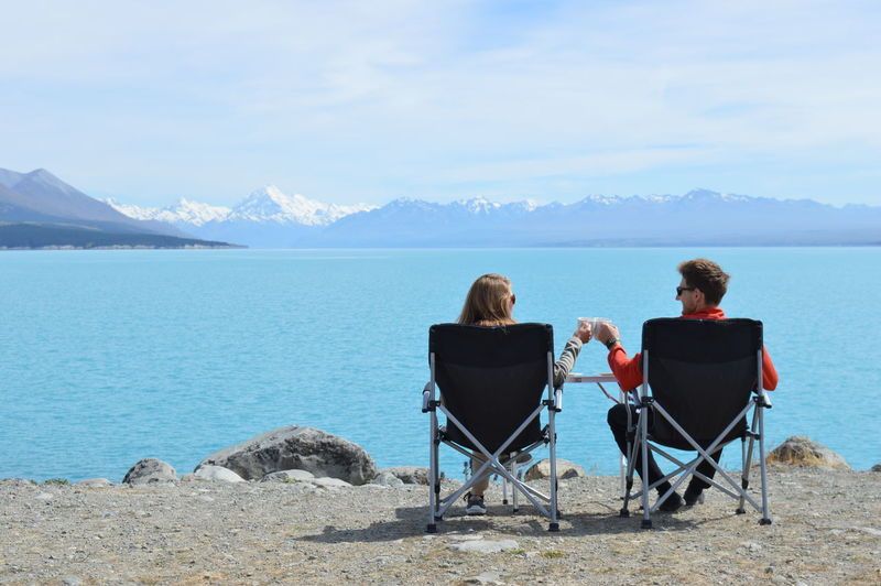 Rear view of couple sitting on chair by lake against sky