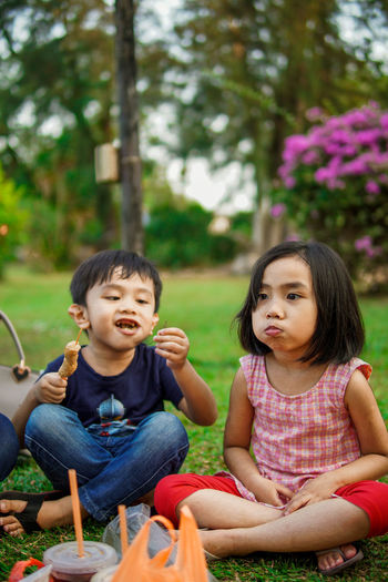 Portrait of a smiling girl and boy sitting outdoors