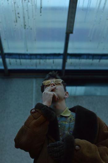 Man smoking cigarette against ceiling