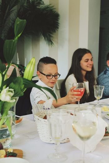 Alcohol Black Hair Celebration Drink Drinking Drinking Glass Eyeglasses  Food And Drink Friendship Happiness Indoors  Leisure Activity Lifestyles Real People Restaurant Sitting Smiling Table Togetherness Two People Wine Wineglass Young Adult Young Men Young Women