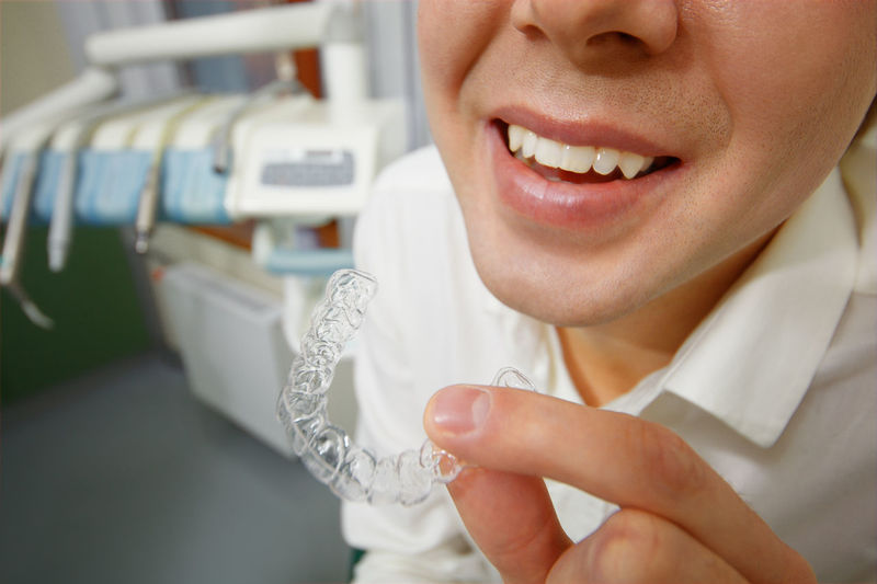 Close-up of dentist holding braces in clinic