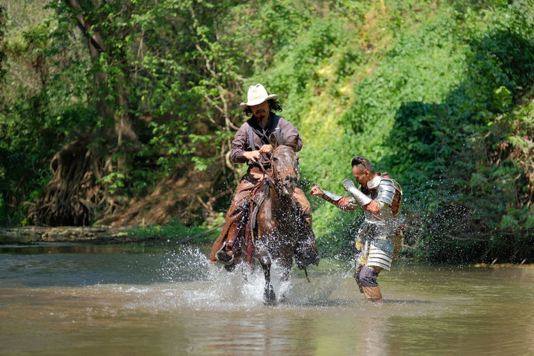 Man standing in lake while warrior riding horses at forest