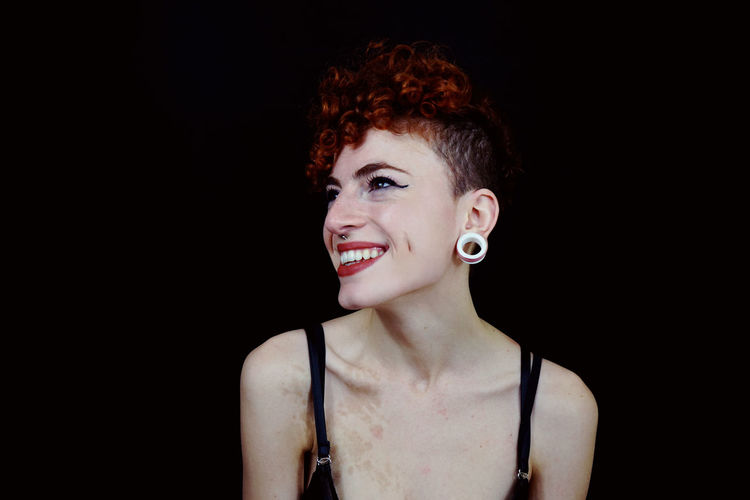 Cheerful Hipster Woman Standing Against Black Background