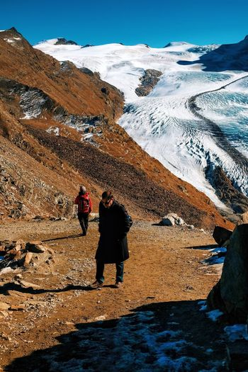 Rear view of people walking on mountain during winter