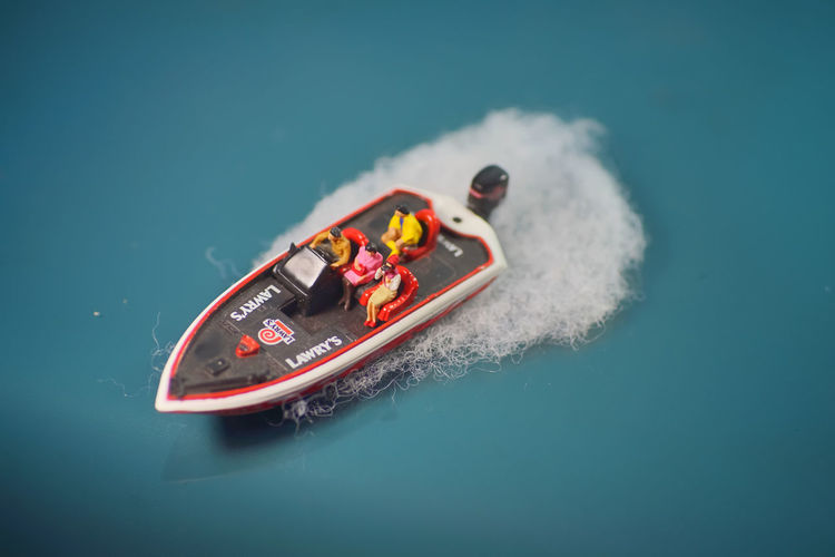 High angle view of toy boat against blue background