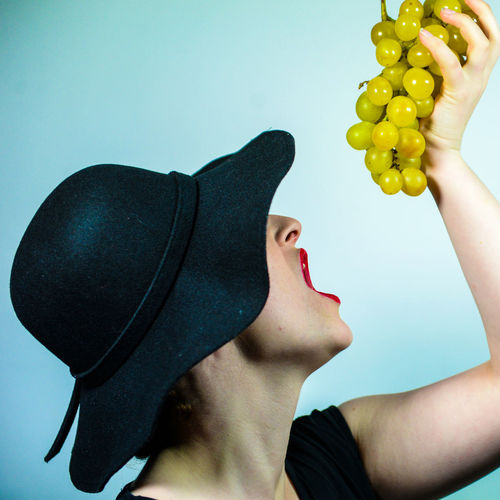 Midsection of man holding fruit against white background